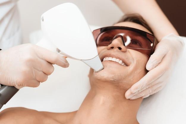 医師は現代のレーザー脱毛器で男性の顔を治療します Premium写真