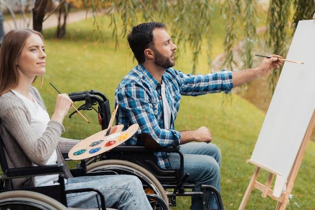 車椅子の病人を持つ男女が一緒に描きます。 Premium写真