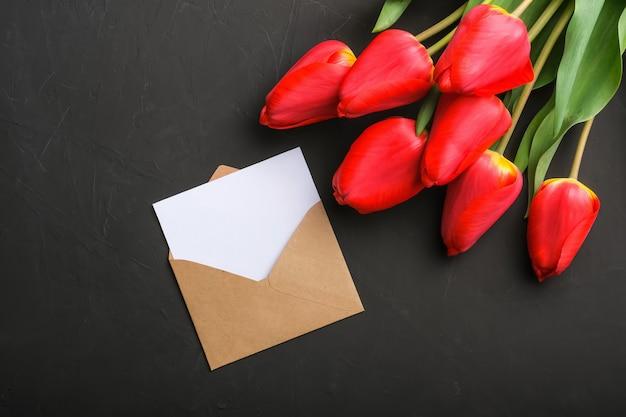 Макет букета из свежих красных тюльпанов и пустая открытка в крафт-конверте Premium Фотографии