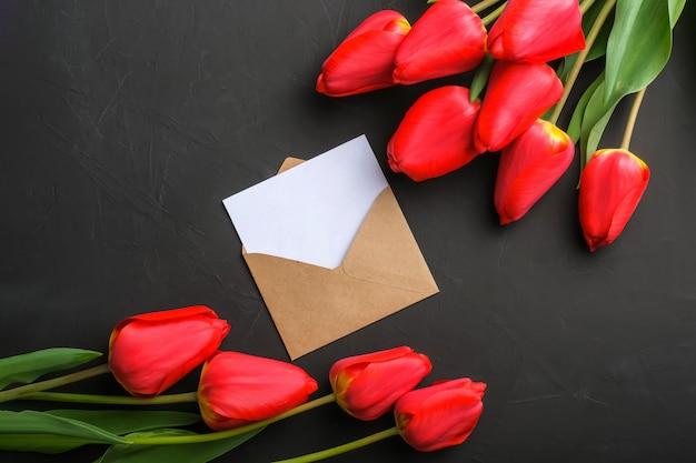 Макет букета из свежих красных тюльпанов и пустая открытка в конверте крафт Premium Фотографии