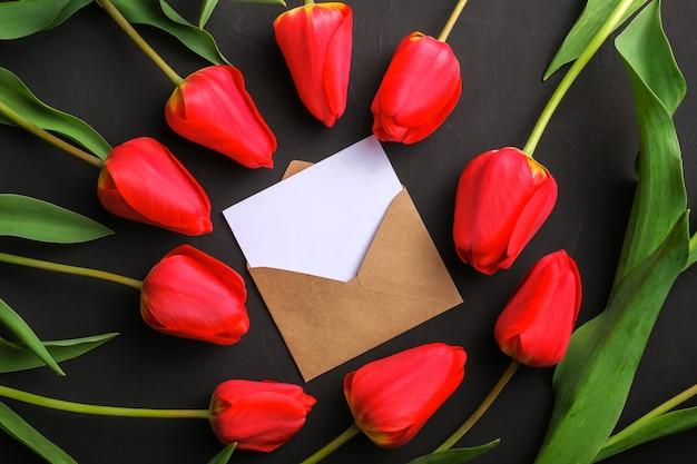 Макет букета из свежих красных тюльпанов и белая пустая открытка в крафт-конверте Premium Фотографии