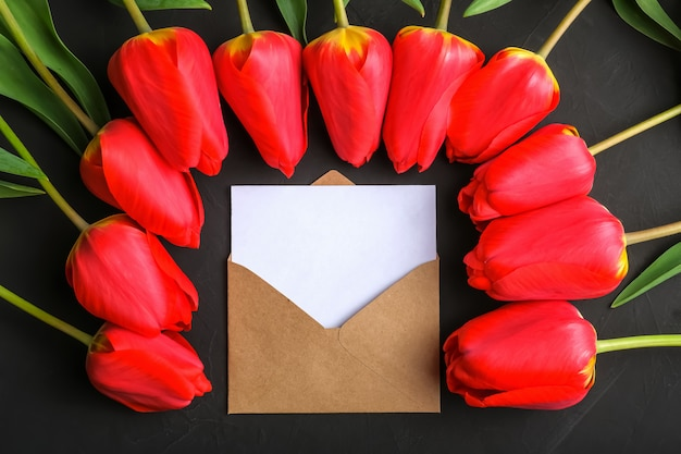Макет букета из свежих красных тюльпанов и поздравительная открытка в крафт-конверте Premium Фотографии