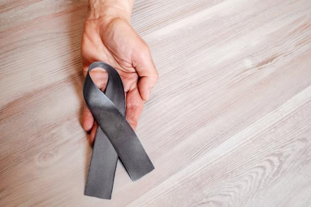 Женская рука держит серую ленту осознания болезни паркинсона. Premium Фотографии