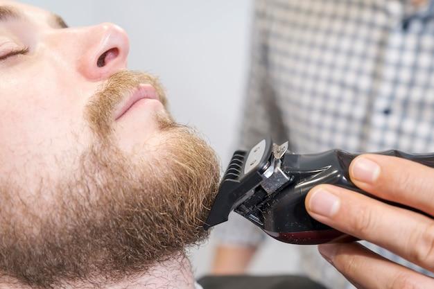 Парикмахер бреет бороду своего клиента электрическим триммером. Premium Фотографии
