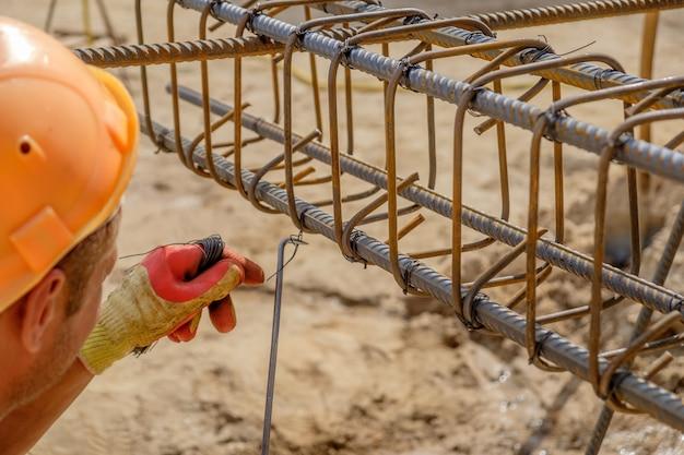 保護手袋の労働者の手は、コンクリート補強用のワイヤーで金属棒を編んでいます。クローズアップビュー Premium写真