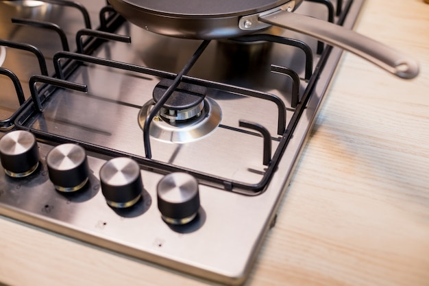 モダンなキッチンに真新しい金属ガスストーブ。電力会社の強制的な節約の概念はストーブです。 Premium写真