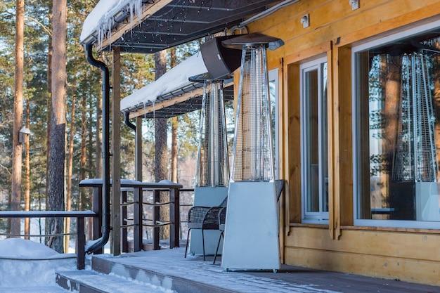 Нагревательная лампа помещается в открытом кафе зимой в течение дня Premium Фотографии