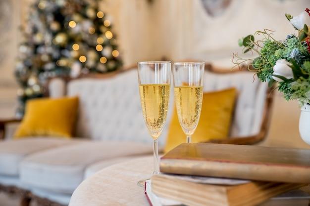 Бокалы для шампанского над золотой мигающей елкой Premium Фотографии