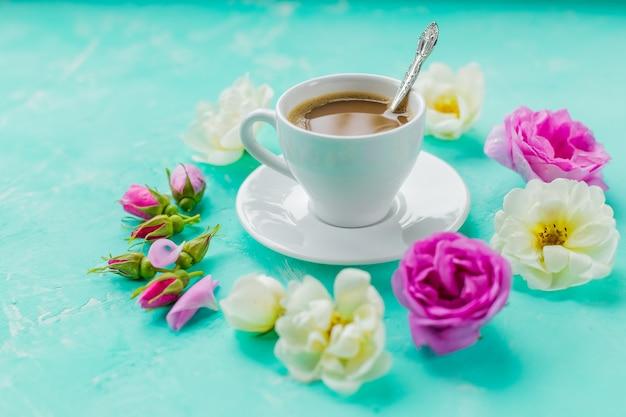 朝一杯のコーヒーと新鮮な美しいピンクと白のバラの花、フラットレイアウト、コピースペース。アメリカーノとコンクリートの背景にバラのカップでコーヒーを飲むコンセプト。朝の女性の背景 Premium写真