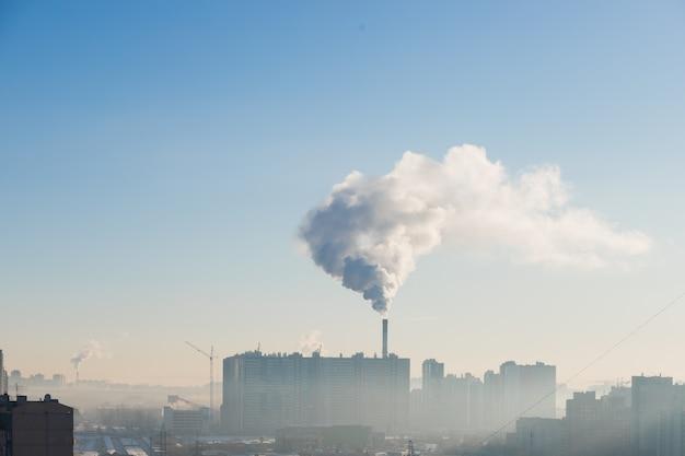 Загрязнение над городом в морозное утро, концепция экологии. ясное голубое небо и дым. заводская труба в облачном небе. городской промышленный вид с птицами. Premium Фотографии