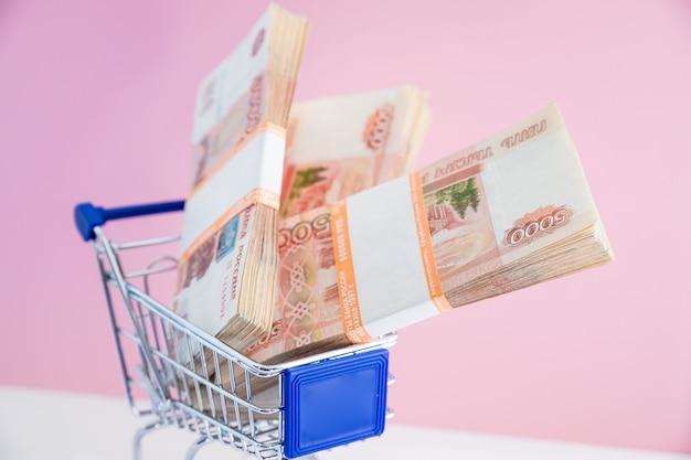 Российский рубль веер в мини-корзине на розовом Premium Фотографии