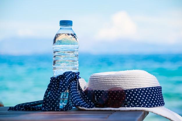 休暇の概念海のビーチでの必需品。飲料水のボトル、夏の白い帽子 Premium写真