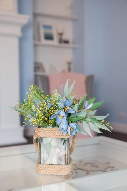ガラステーブルの上に花瓶の春の花 Premium写真
