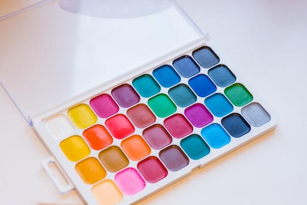 水彩絵の具箱。ペイントブラシでカラー塗料。学校のコンセプトに戻る子供たちの絵の概念。子供たちの芸術上面図。スペースをコピーします。 Premium写真