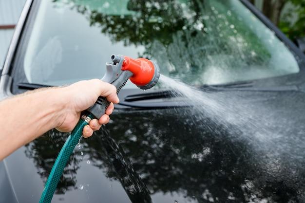 シャンプーストロークを残してセルフサービス洗車、ブラシで彼の車を掃除する人 Premium写真