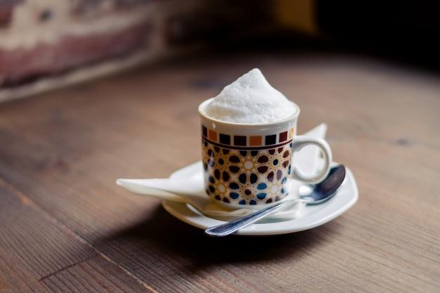 木製のテーブルに分離されたコーヒーのカップ。レトロなスタイル。 Premium写真