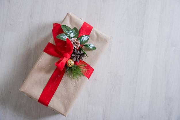 木材に分離されたクリスマスの赤いリボンと結ばれるクラフトペーパーギフトボックス Premium写真
