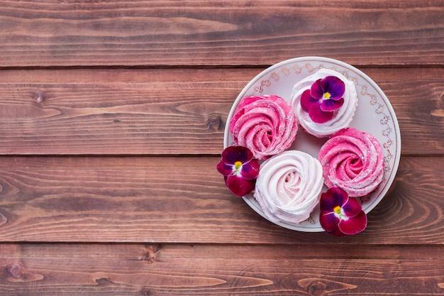 ピンクの花で飾られたピンクのマシュマロ。 Premium写真