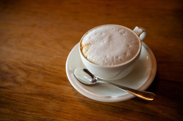 木製のテーブルのトップビューで新鮮なホットコーヒー。 Premium写真