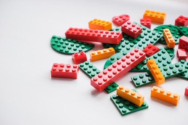 パイルプラスチックのおもちゃのブロック。デザイナーの多色のプラスチックビルディングブロック。子供のコンストラクタ、キューブ。記憶と心を発達させる運動のためのゲーム。 Premium写真