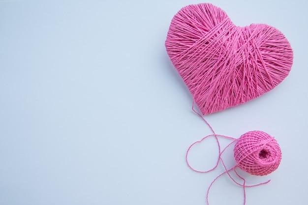 カラフルな糸玉が分離されました。愛のシンボルのようなピンクのハート。趣味。コピースペース Premium写真