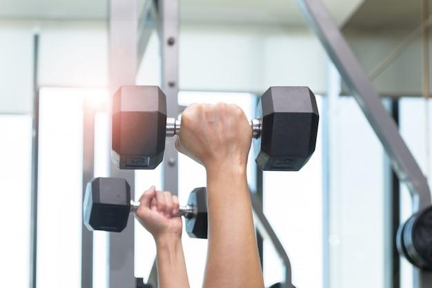 男性の手のクローズアップは、ダンベルを持ち上げることによって運動しています。フィットネスルームで Premium写真