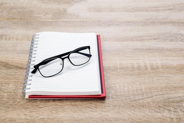 コンセプト教育またはビジネス:木製のテーブルに黒のメガネで日記やメモ帳を開きます。 Premium写真
