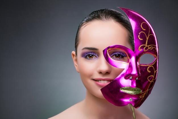 カーニバルマスクを持つ若い女 Premium写真