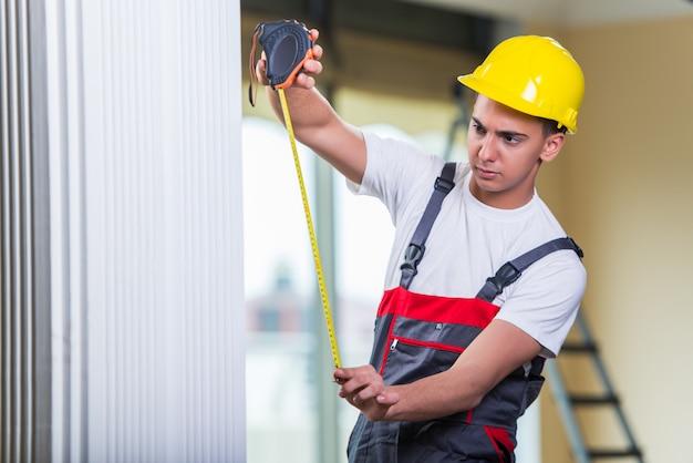 Молодой ремонтник с рулеткой работает на ремонт Premium Фотографии