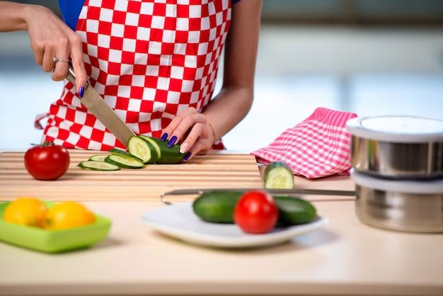 女性が台所でサラダを準備します。 Premium写真