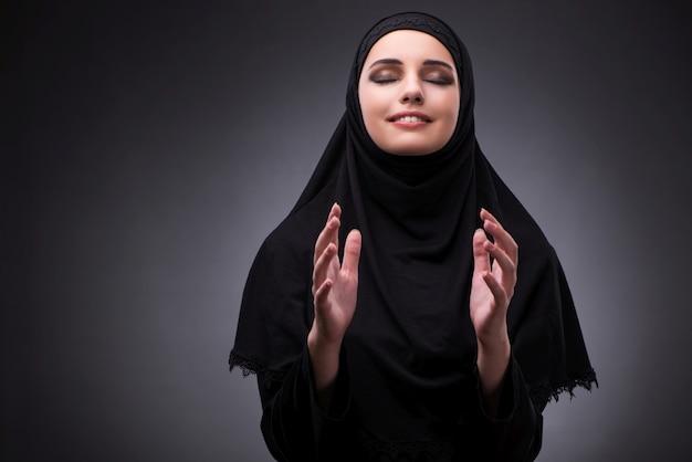 暗い背景に対して黒のドレスでイスラム教徒の女性 Premium写真