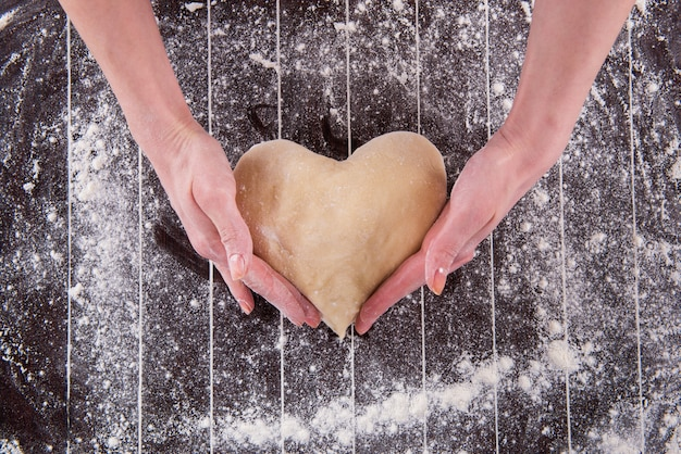 Повар готовит тесто для выпечки на кухне Premium Фотографии