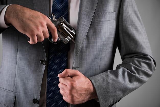 Мужчина достает пистолет из кармана Premium Фотографии