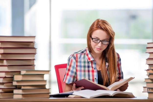 試験の準備の書籍のスタックを持つ学生 Premium写真