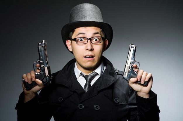 Преступник в черном плаще держит гадган против серого Premium Фотографии