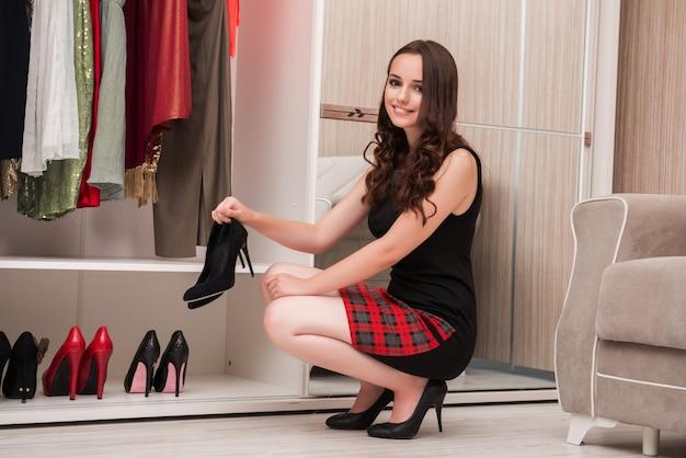 若い女性の夜のパーティーのための服を選ぶ Premium写真