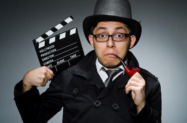 Детектив в черном плаще с с 'хлопушкой' на сером Premium Фотографии