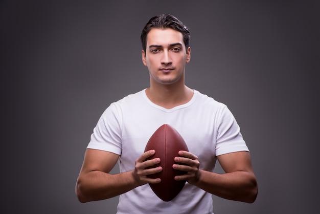 スポーツコンセプトでアメリカンフットボールを持つ男 Premium写真