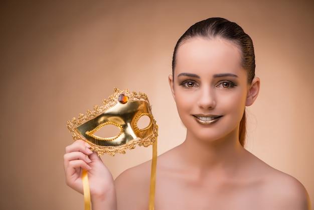 カーニバルの概念でマスクを持つ若い女 Premium写真