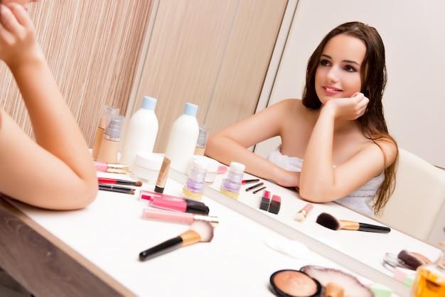 Женщина делает макияж дома готовится к вечеринке Premium Фотографии