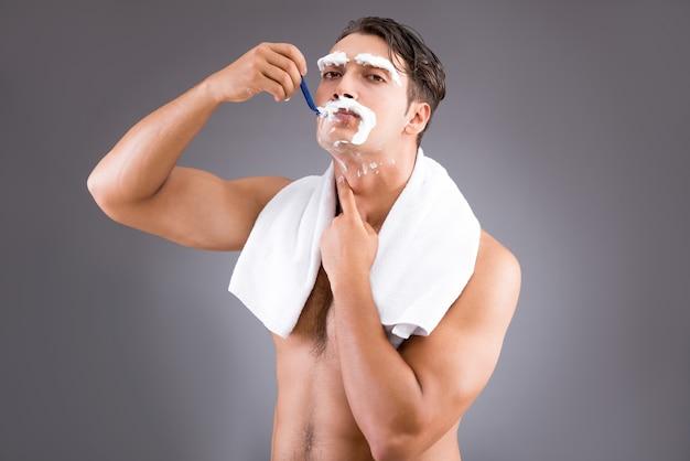 Красивый мужчина бритья против темноты Premium Фотографии