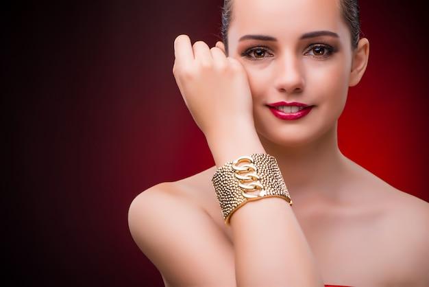 Женщина с золотым браслетом в концепции красоты Premium Фотографии