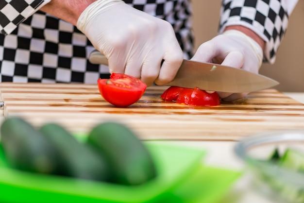 男性の料理人が台所で食べ物を準備する Premium写真