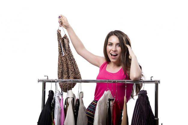女性の白で隔離される店で服を選ぶ Premium写真