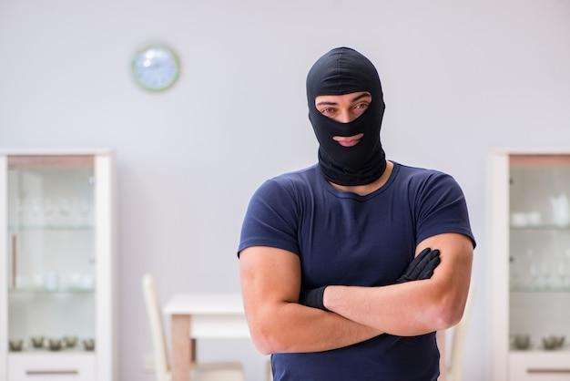 貴重なものを盗む目出し帽を身に着けている強盗 Premium写真