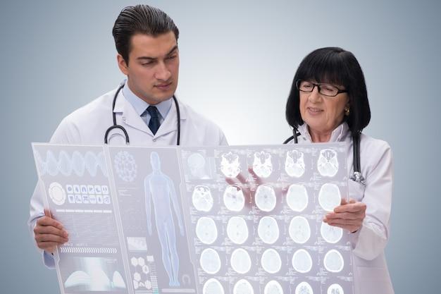 Женщина и мужчина врач смотрит на мрт Premium Фотографии