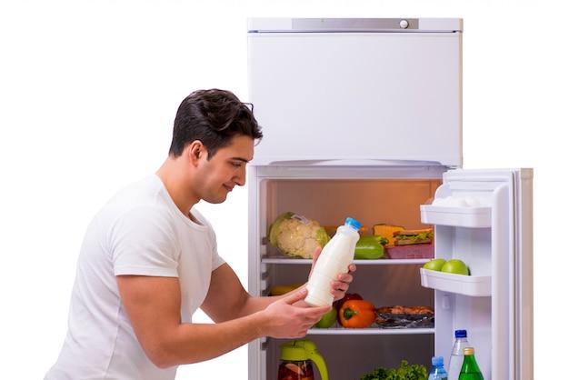 食品がいっぱい入った冷蔵庫の横にある男 Premium写真