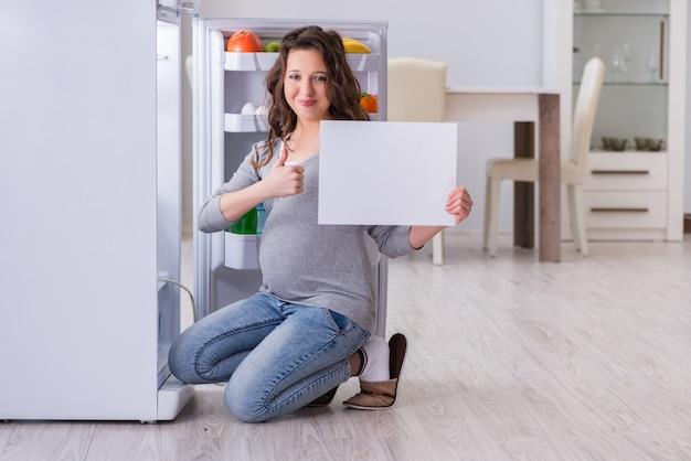 Беременная женщина возле холодильника с пустым сообщением Premium Фотографии