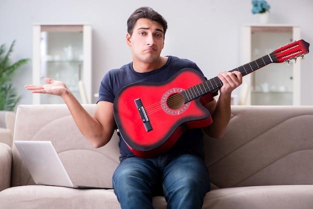 若い男が自宅でギターを弾く練習 Premium写真