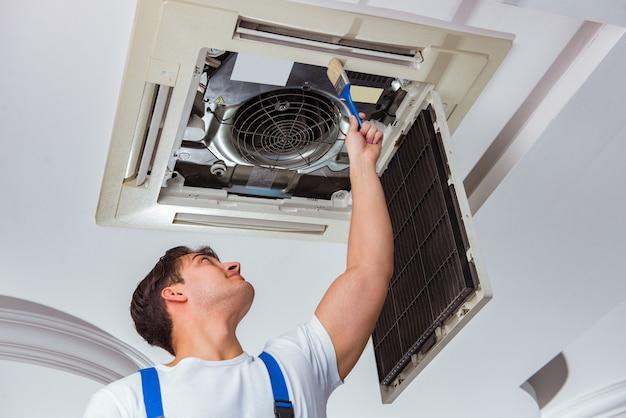 天井のエアコンユニットを修復する労働者 Premium写真